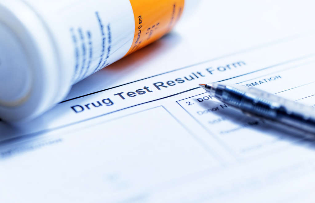 Drug Test Results Form with Pill Bottle and Pen