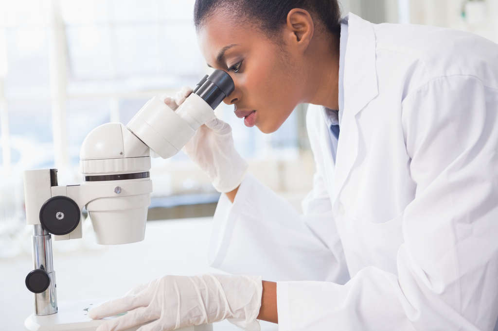 Woman lab tech looking into microscope