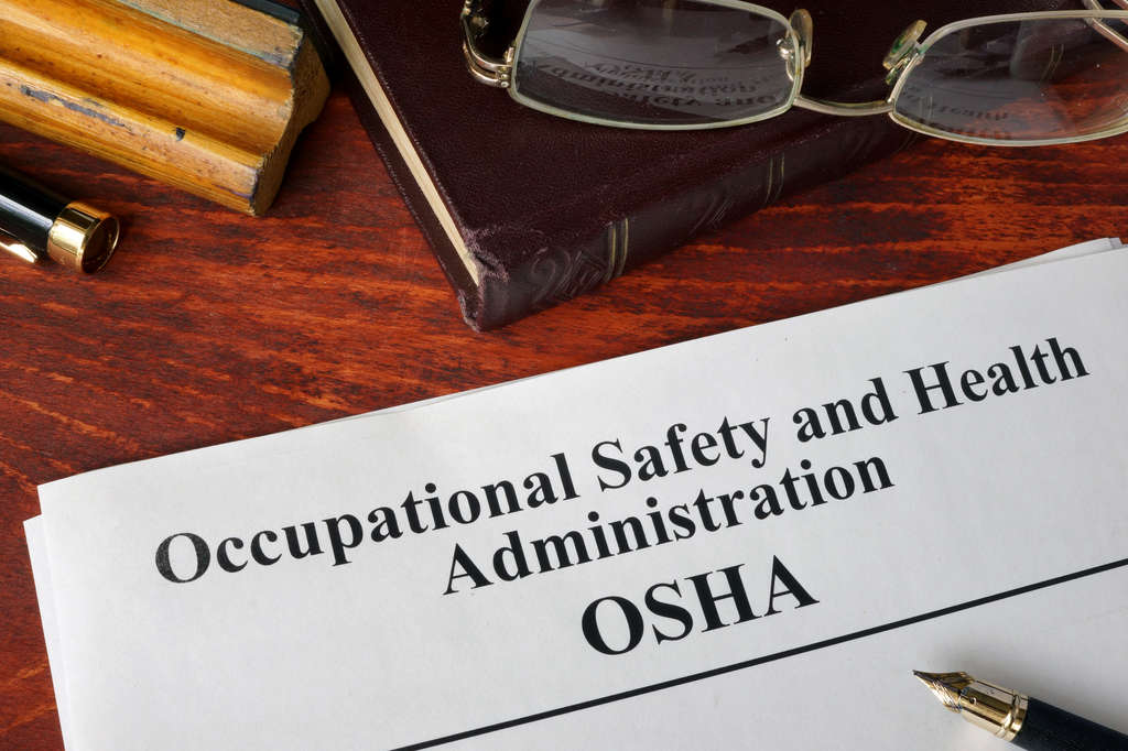 OSHA document on table with book, glasses & pen