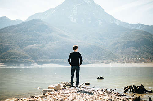 man standing by river and mountain
