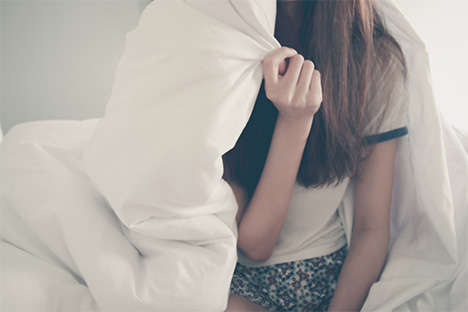 woman covering face with comforter
