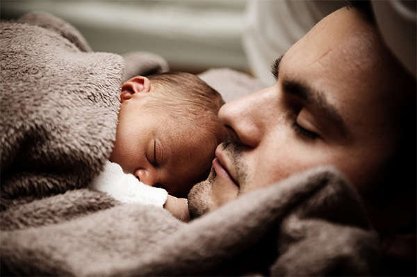 man napping with newborn